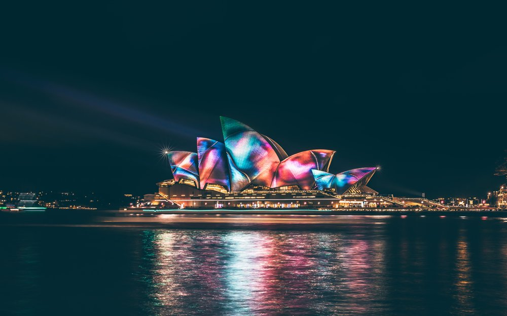 Sydney Opera House looking lit up at night with a range of colors for the Viviv Sydney