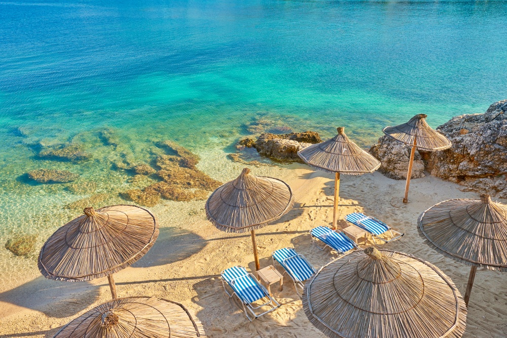 beautiful coast of Albanian Riviera with lounge chairs on the sand