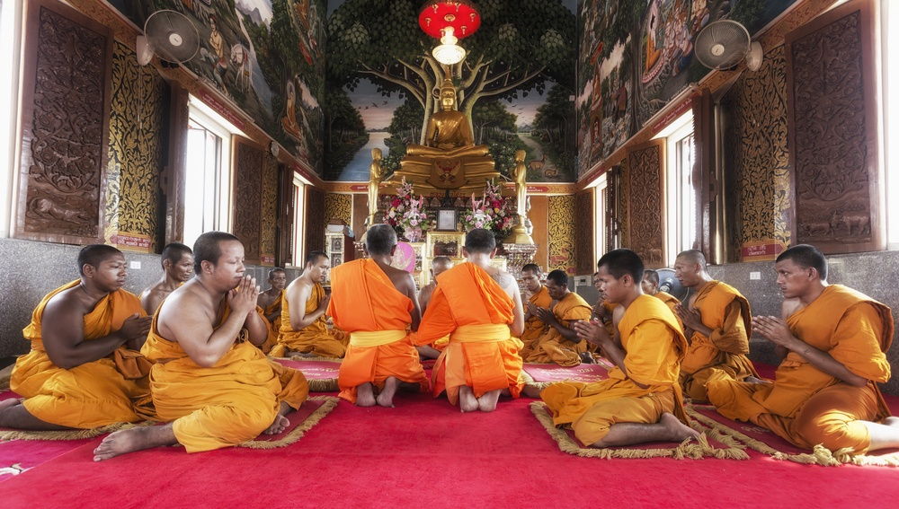 group of monks huddled in monastery in cambodia praying