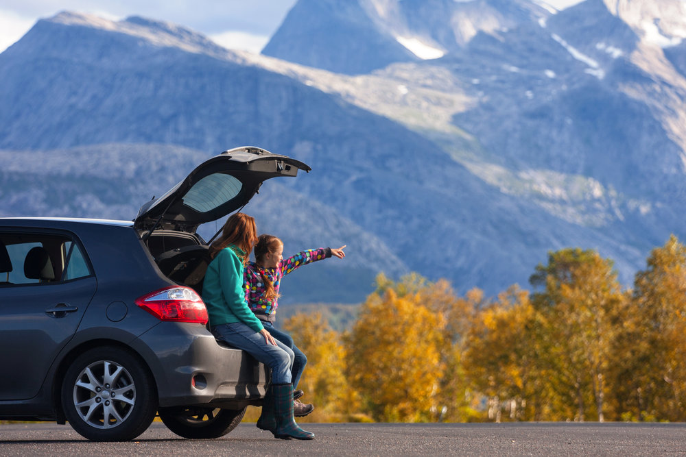 young girl with mom sitting on the car pointing at the beautiful mountain scenery