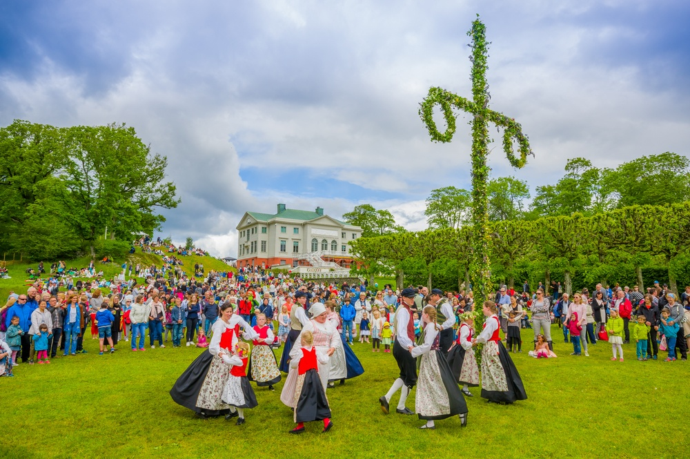 midsummer celebration in sweden outside on a field by a house
