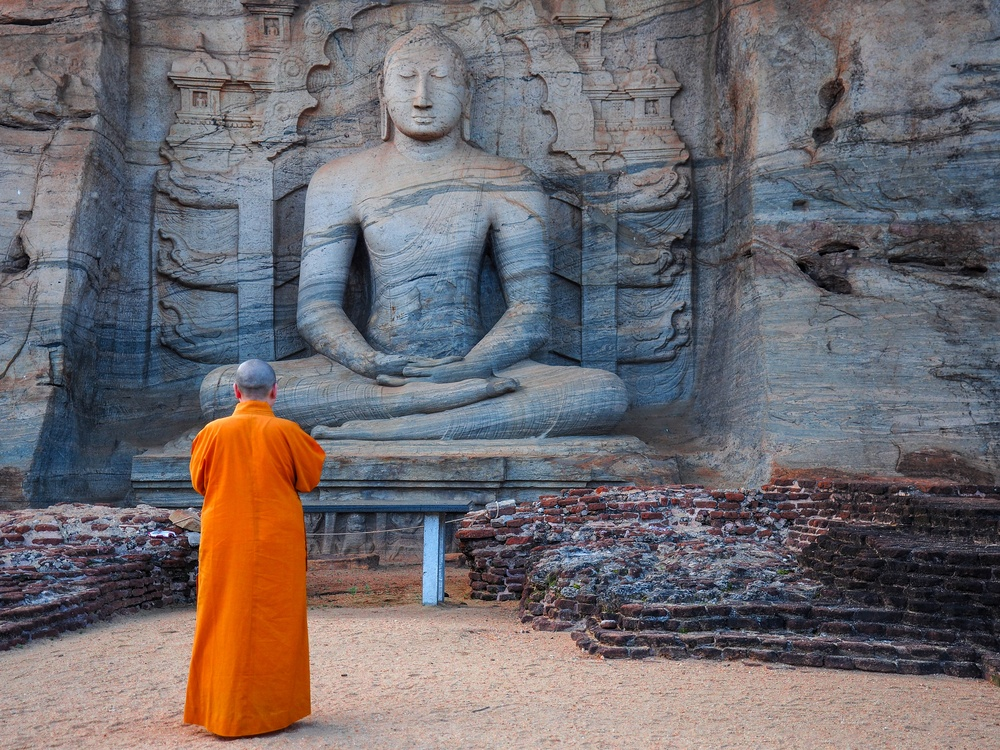 buddhist monk meditating in front of monument carving