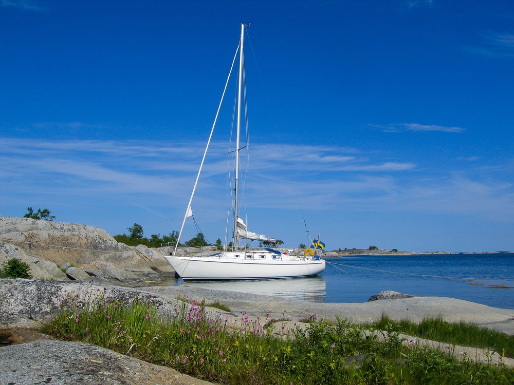 sailboat tied to shore in stockholm's archipelago in sweden
