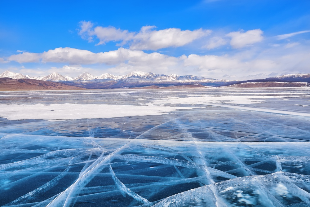 vast ice glacier in front of snow capped mountains where the lake khuvsgul ice festival is held in Mongolia
