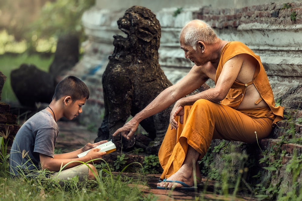 old monk in cambodia teaching young apprentice out of a book