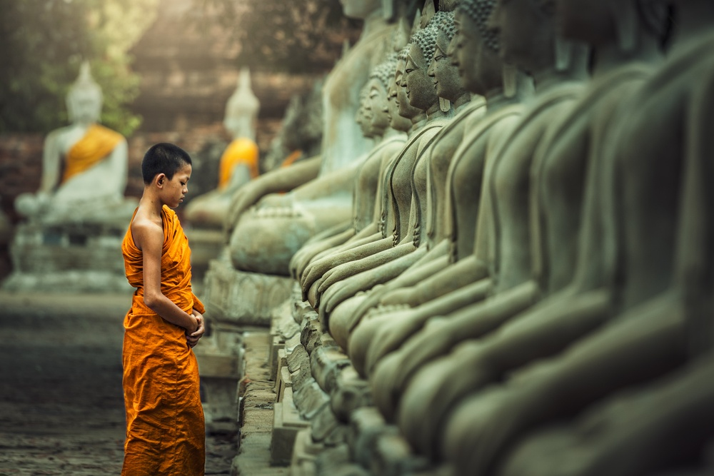 young monk in cambodia praying and paying his respects to statues of his gods