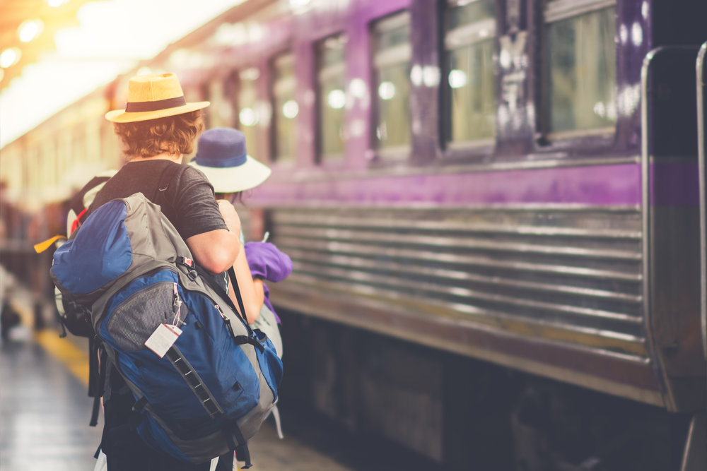 backpacker looks at train passsing by ready to get onboard