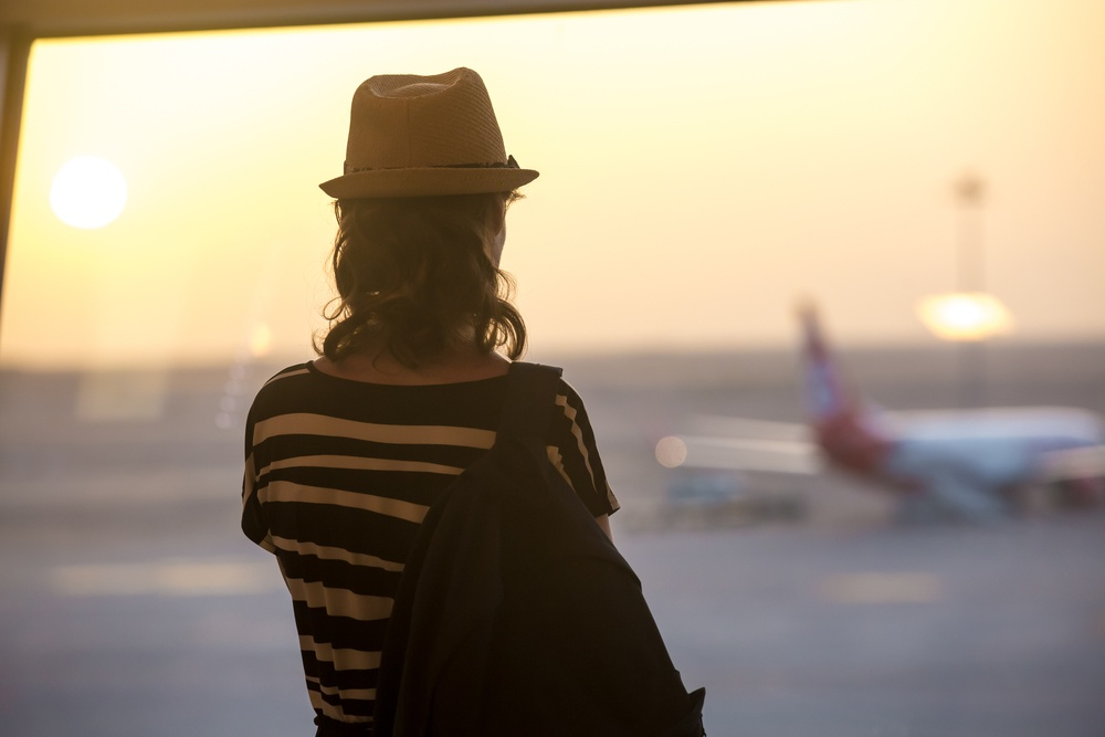 woman looking at the runway at an airport before traveling