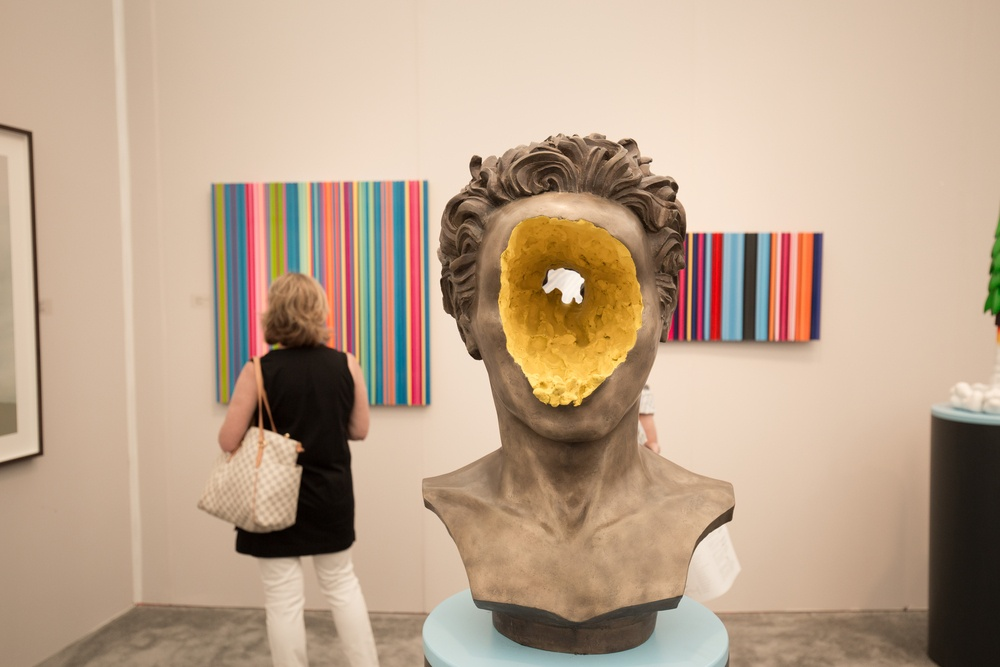 odd art exhibit showcasing a head statue with a hole through it at Art Basel in Miami Beach