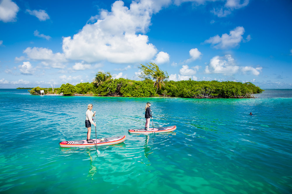 two young women standing on paddle boards around a tiny island on the ocean