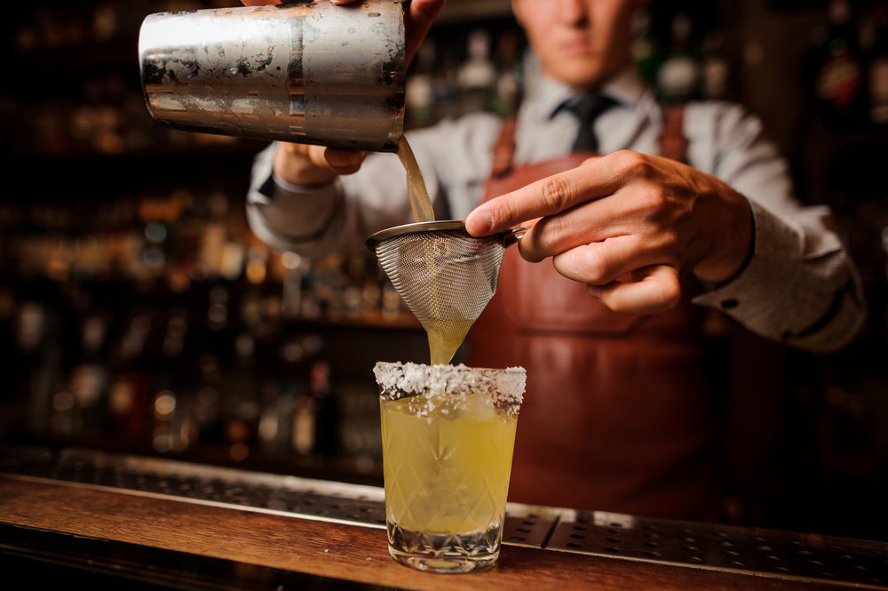 bartender pouring a yellow cocktail at a bar