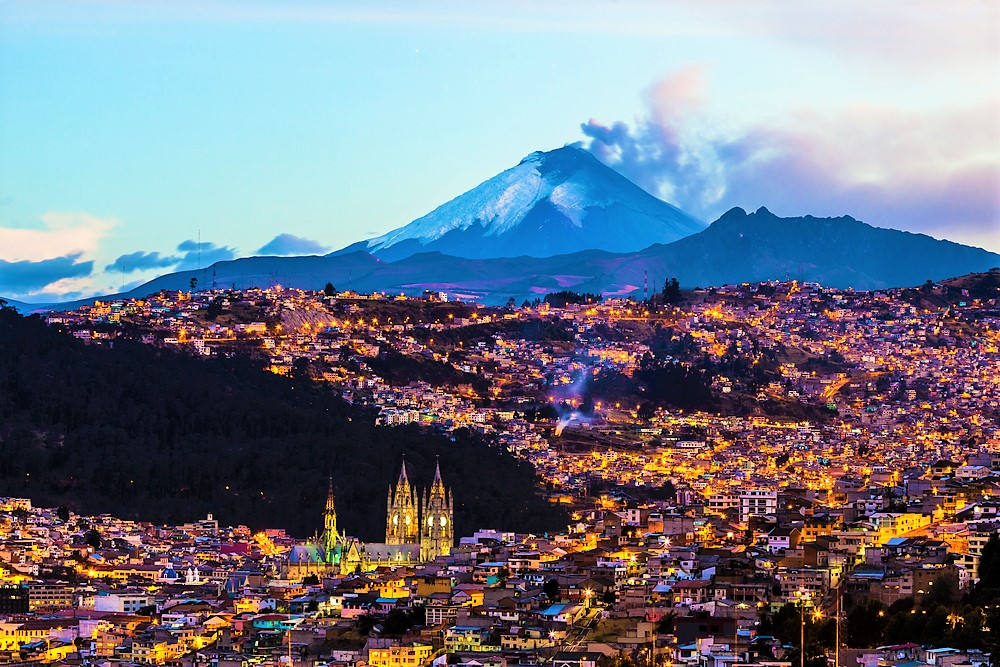 stunning view of Quito at night with the backdrop of the snow covered mountains in Ecuador