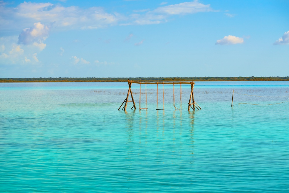 wooden swingset in the middle of the water off the coast of Bacalar, Mexico