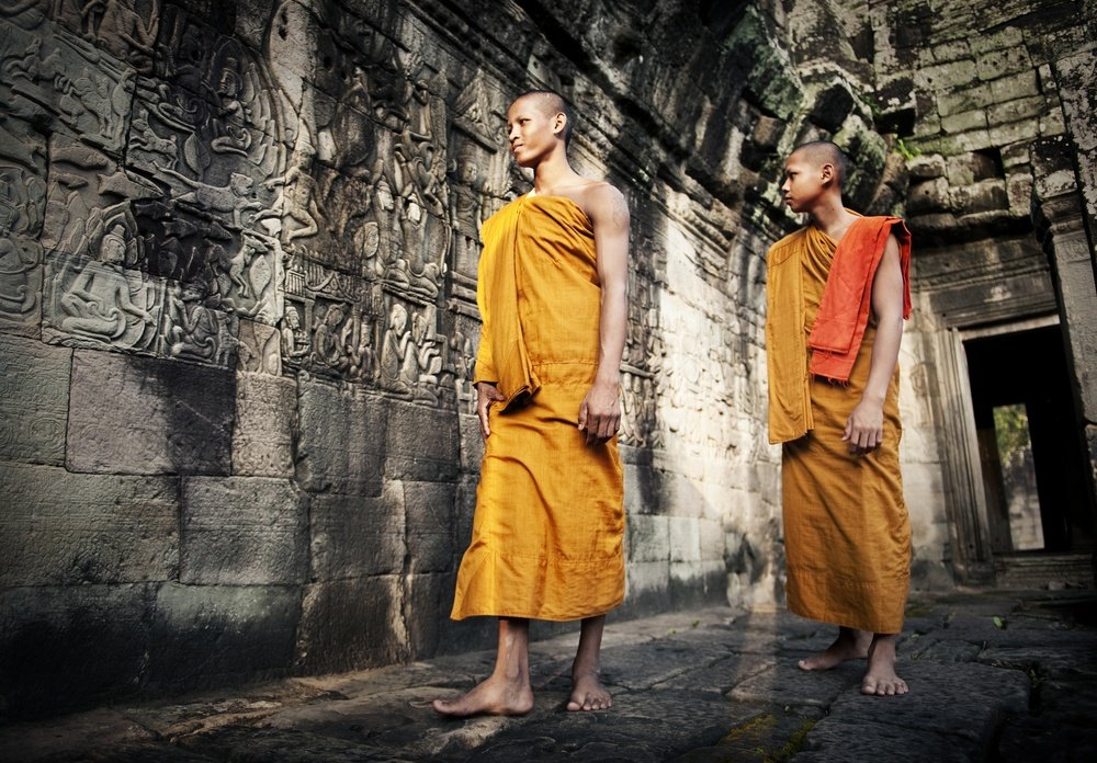two young buddhist monks walking through an old monastery passing by carved stone walls