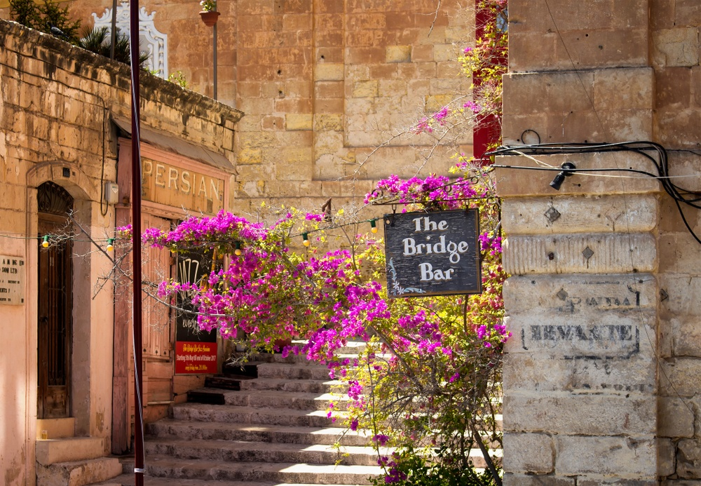 cute cobblestone street in valletta with bar sign and flowers