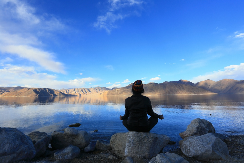 girl doing yoga by the lake in ladakh india
