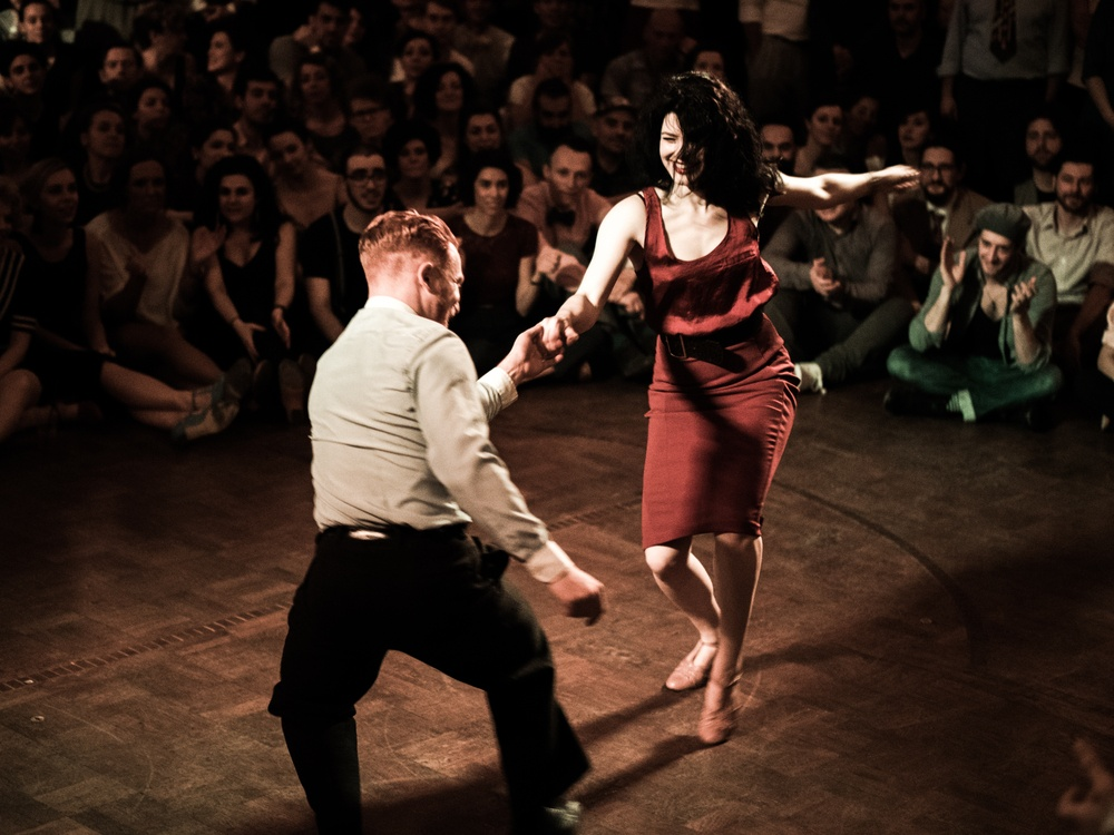 Man and woman tango dance while surrounded by people watching, smiling, clapping, solo travel