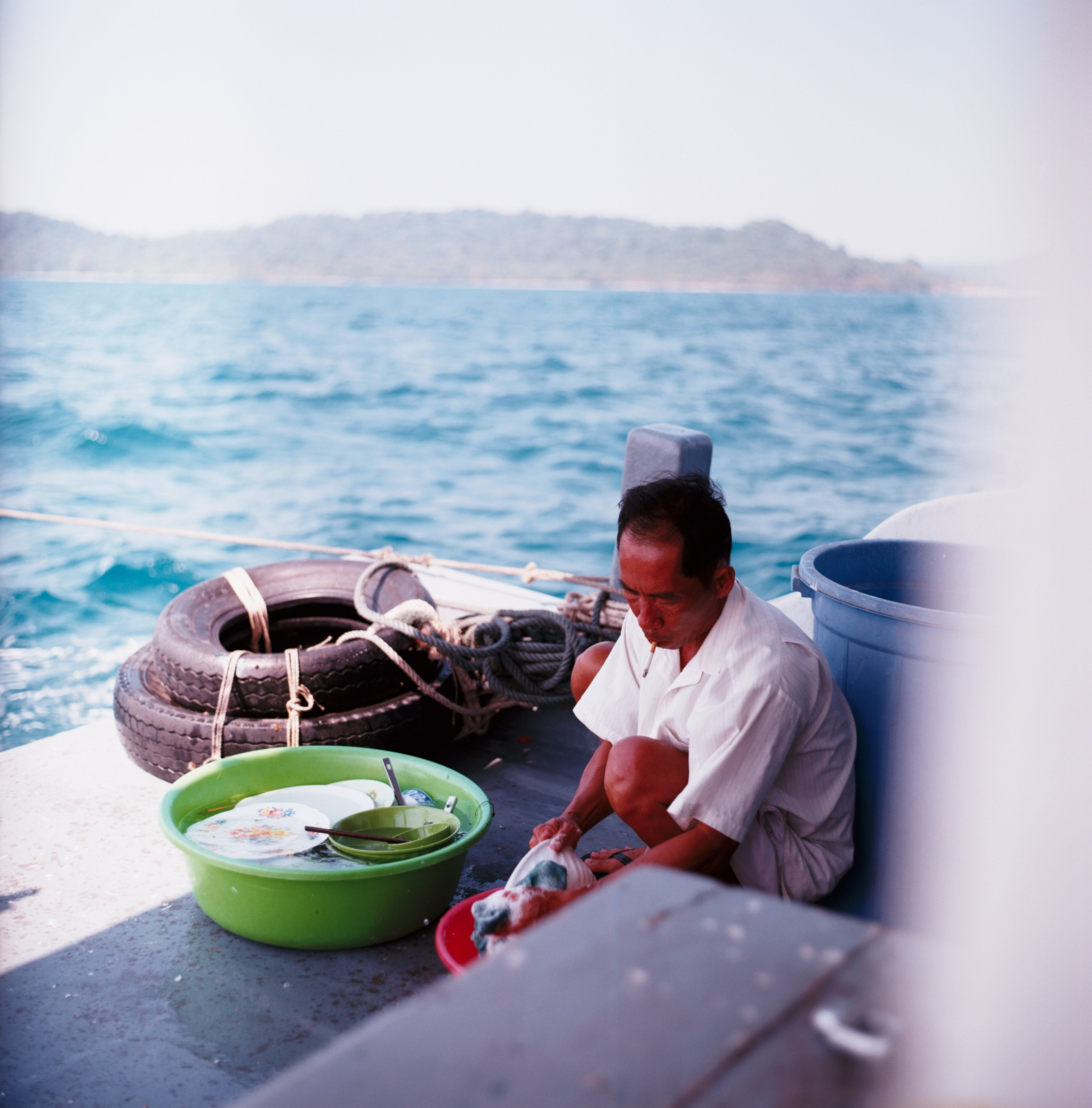 old man going about his work on the boat in Vietnam ocean