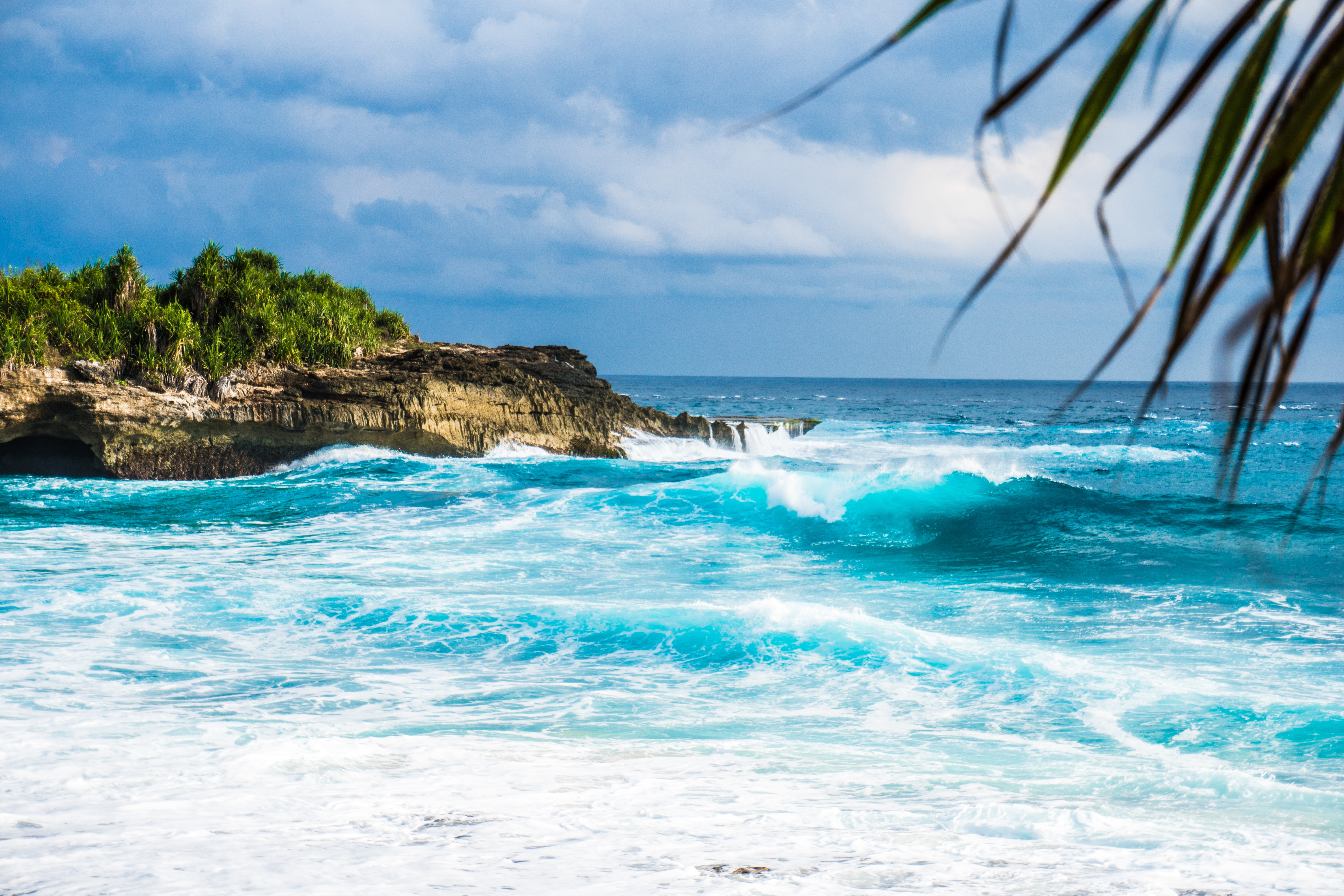 Breathtakingly blue waves crashing into rocky shore - Lembongan island, Indonesia