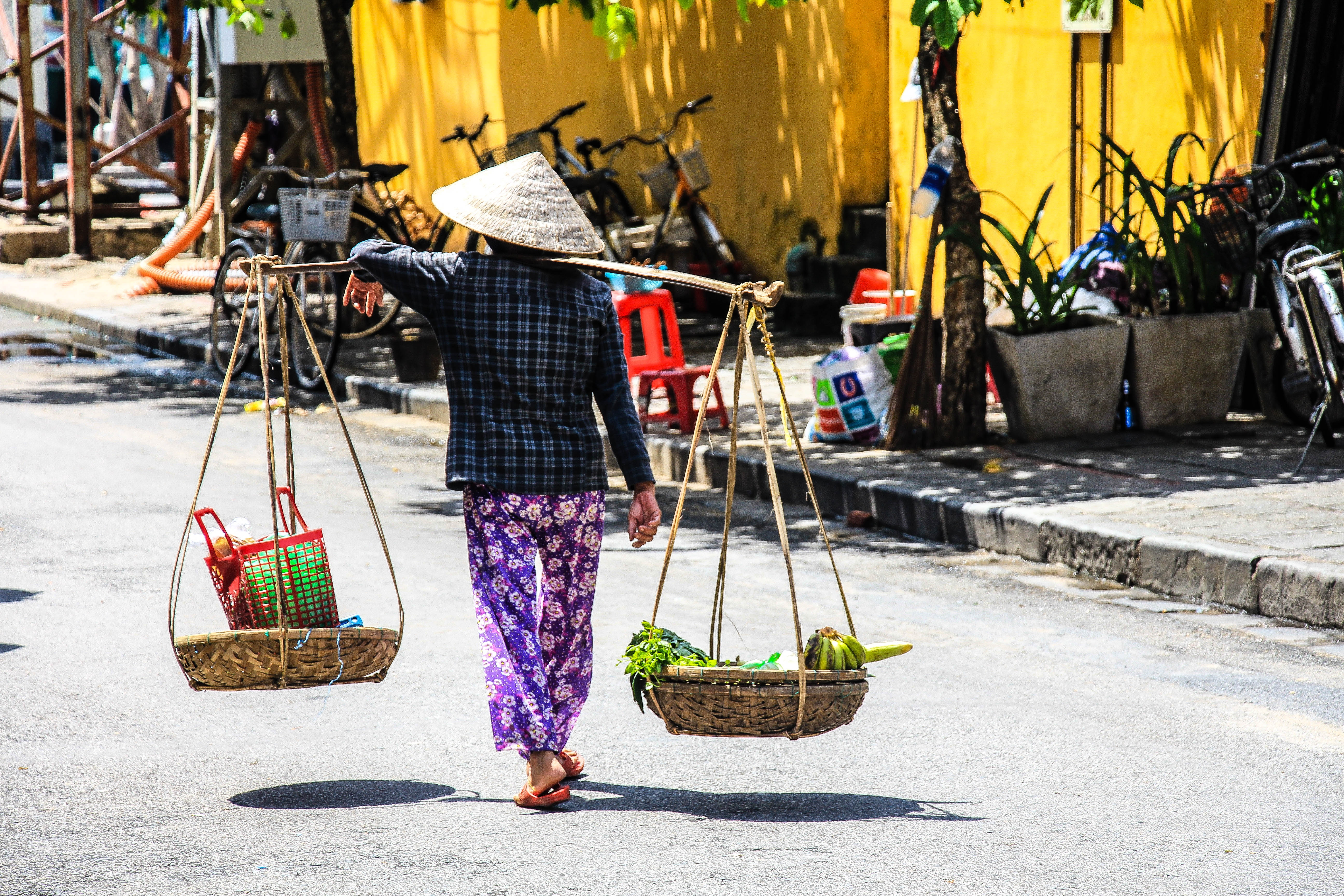 a look into an everyday scene in Vietnam - a woman carries her vegetable produce home in balance