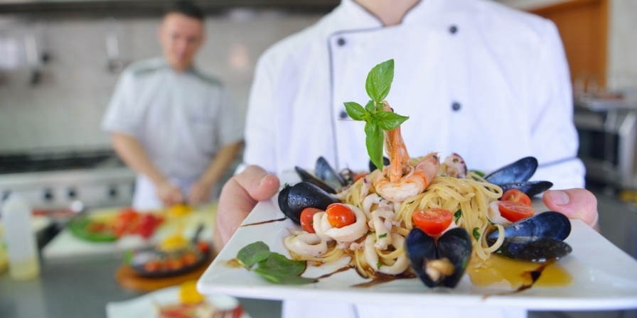 Handsome chef dressed in white uniform decorating pasta salad and seafood fish in modern kitchen-768706-edited.jpeg