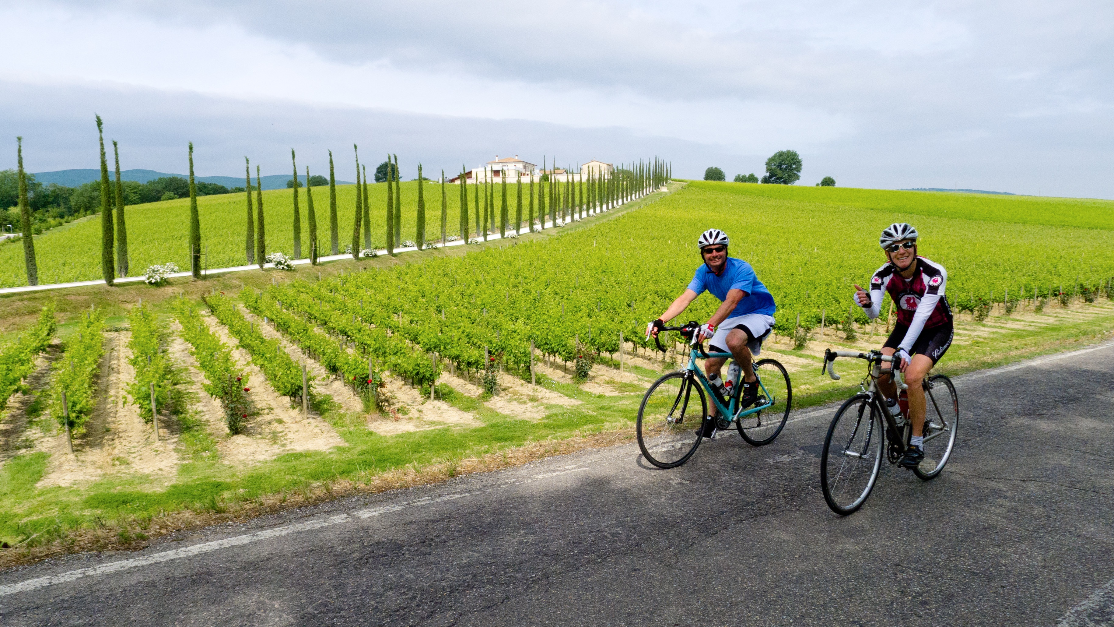 A photograph of two cyclists riding through rolling hills in Italy.