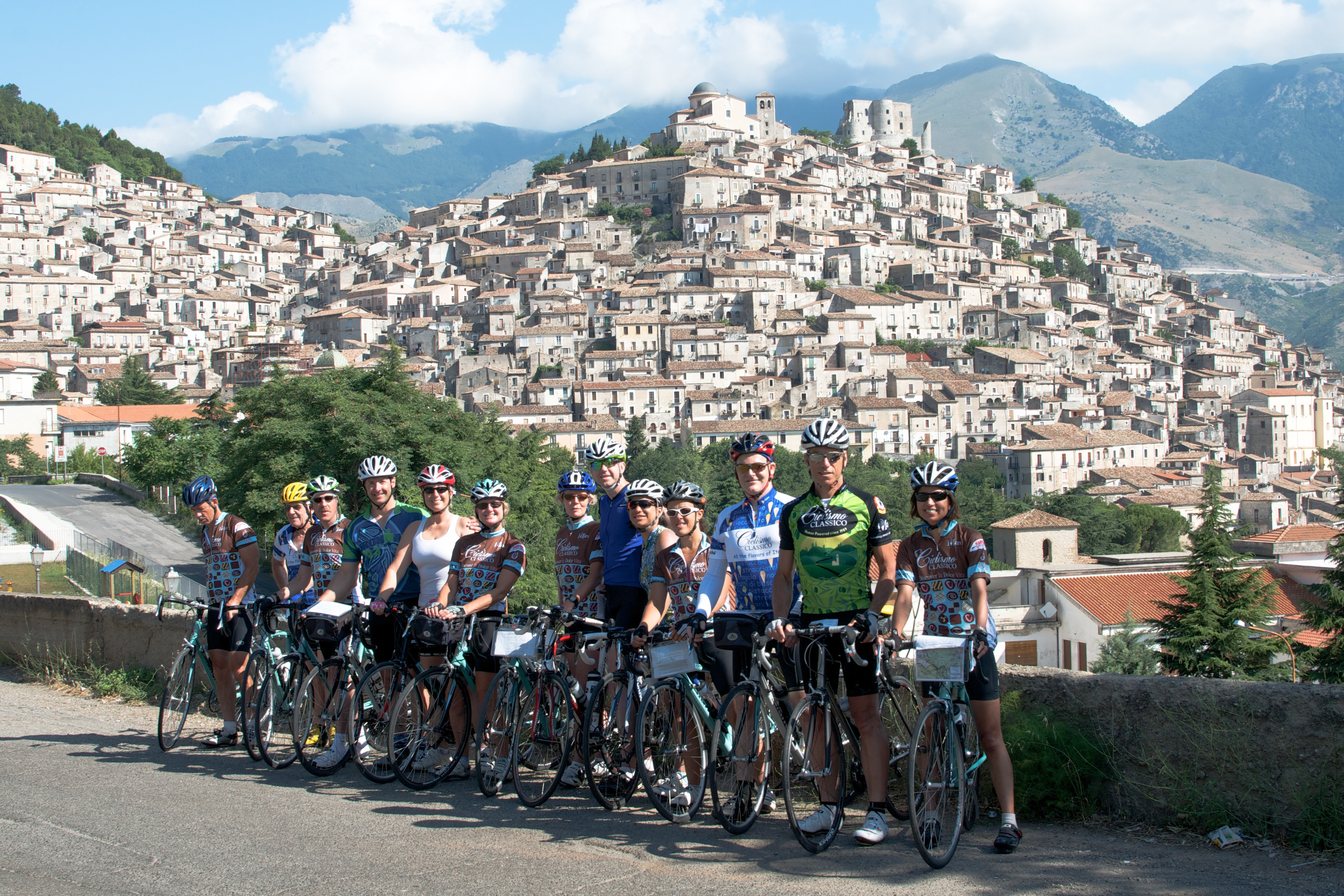 A photograph of a group of cyclists posing for a group photo on a road in Italy.