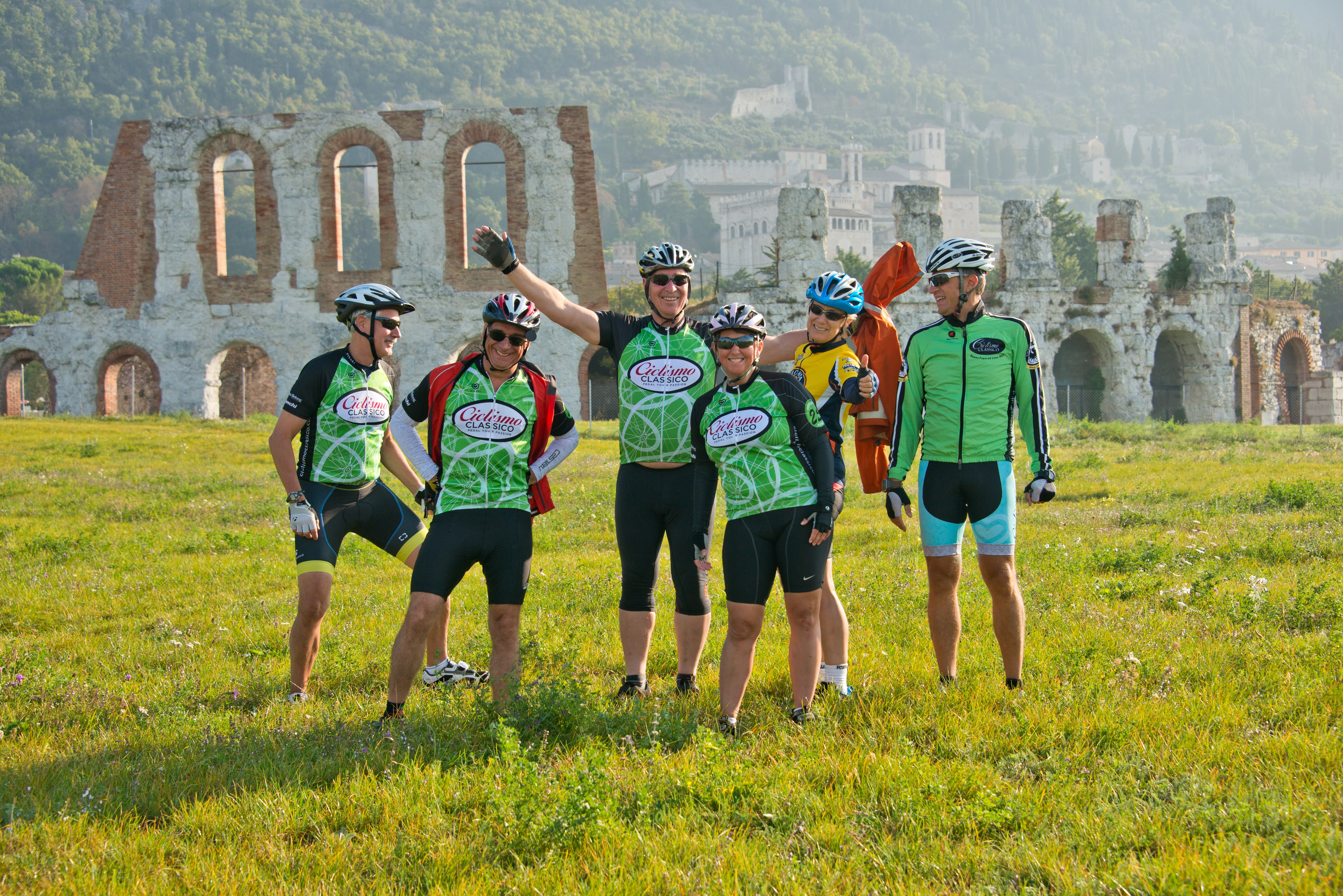 A photograph of a group of cyclists posing in front of medieval ruins.
