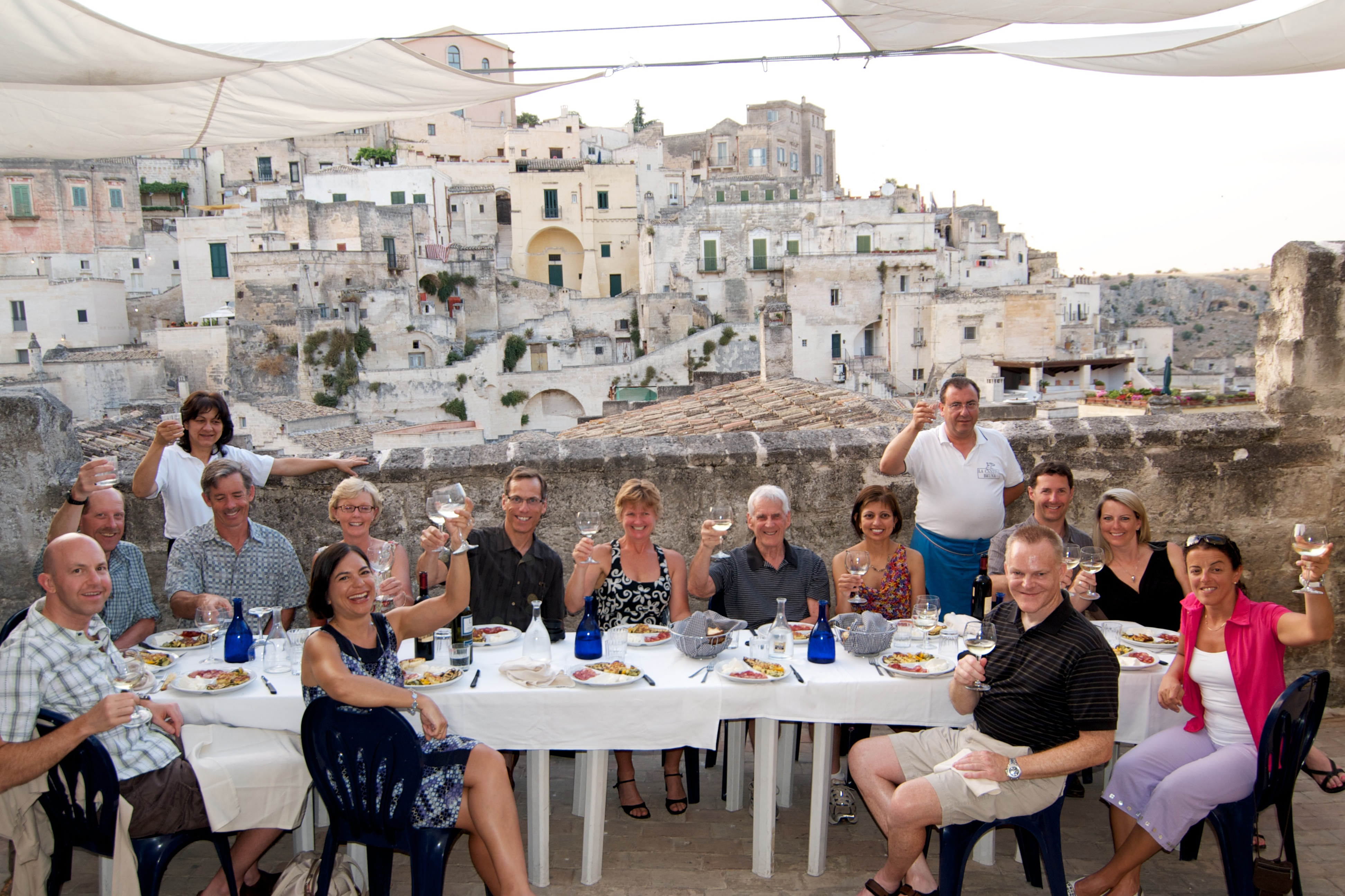A photograph of a group of cyclists enjoying dinner in Italy.