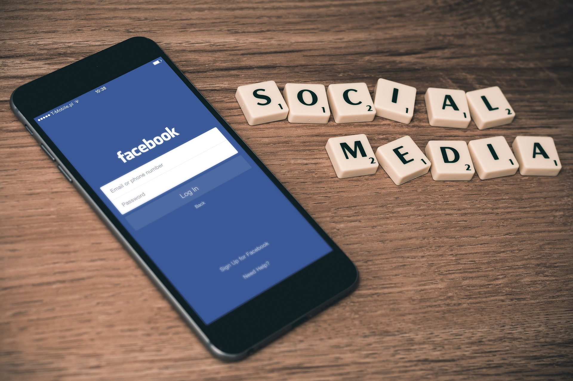 """A phone showing Facebook login screen and Scrabble tiles spelling """"social media"""""""