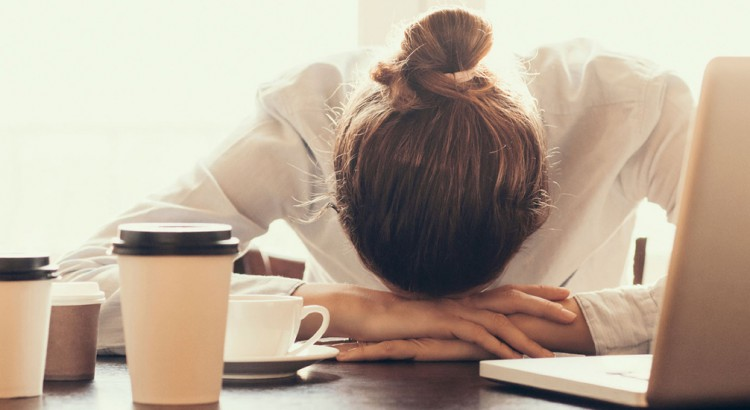 Woman-with-her-head-down-on-her-desk-and-several-coffee-cups