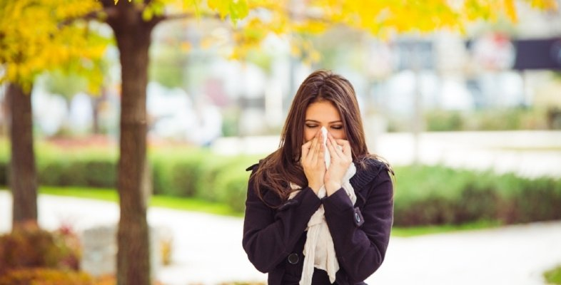 woman-sneezing-outside-fall-day