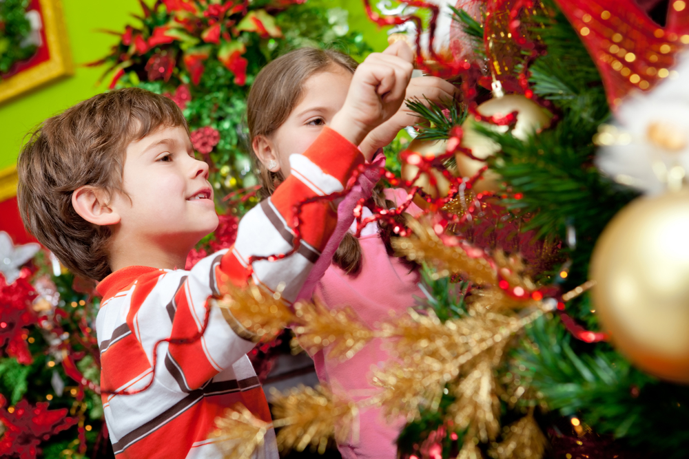 Happy kids decorating a Christmas tree with ornaments
