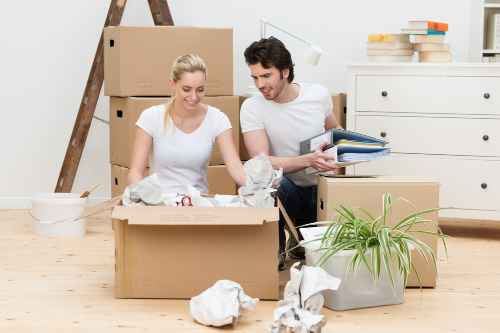 Happy young couple unpacking in their new home kneeling on a bare wooden floor unwrapping items from a large brown cardboard box