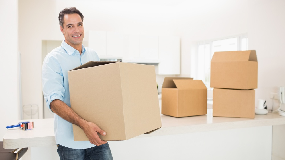 Portrait of a smiling man carrying boxes in a new house