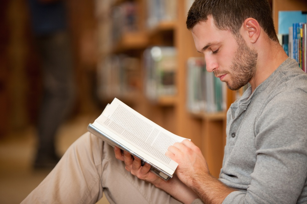Serious male student reading a book in a library