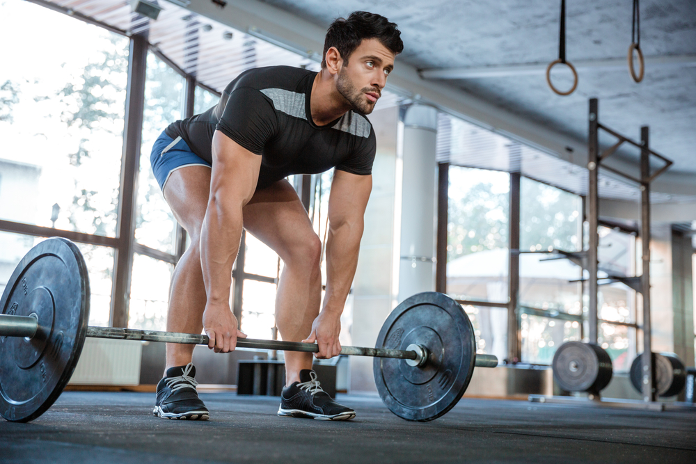Athlete wearing blue shorts and black t-shirt lifting big barbell