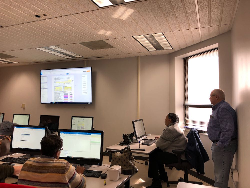 A government IT tech team gathers for training on government form automation software from SeamlessDocs.