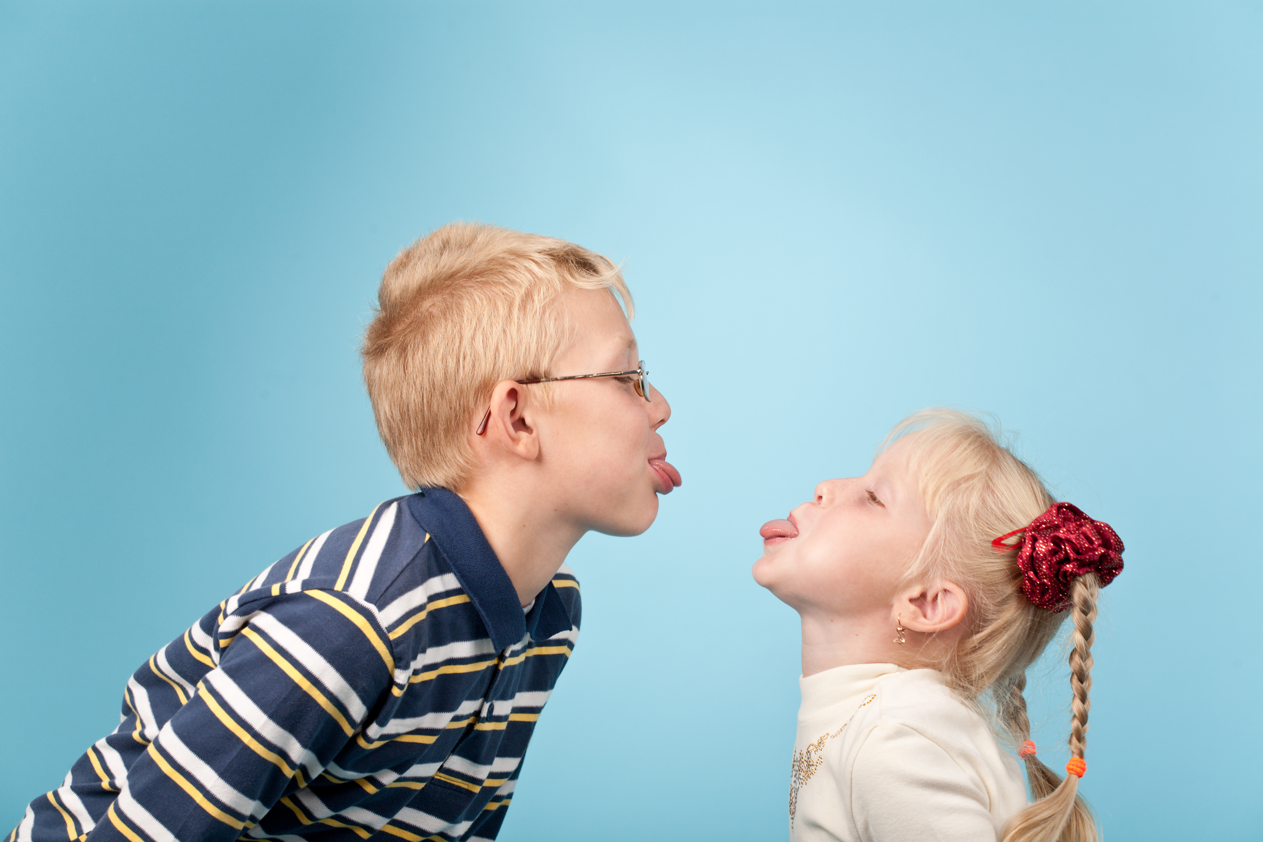 Canva - A boy and girl sticking their tongues out at each other
