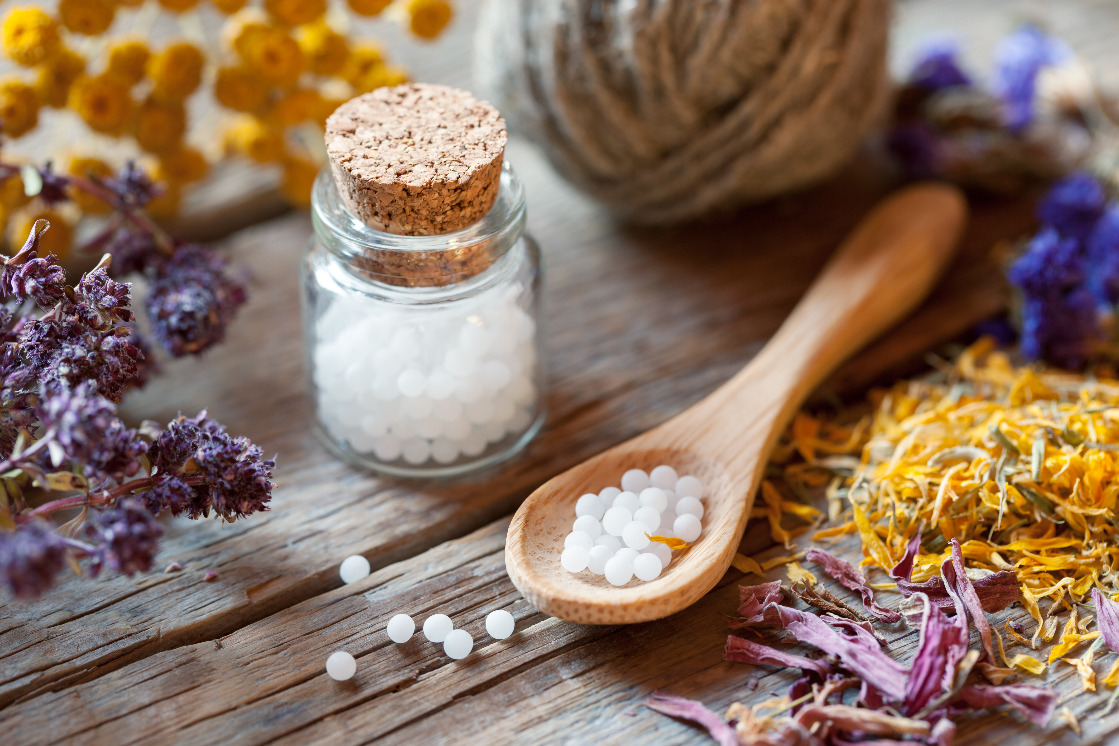 Canva - Bottles of homeopathy globules, spoon and healthy herbs.