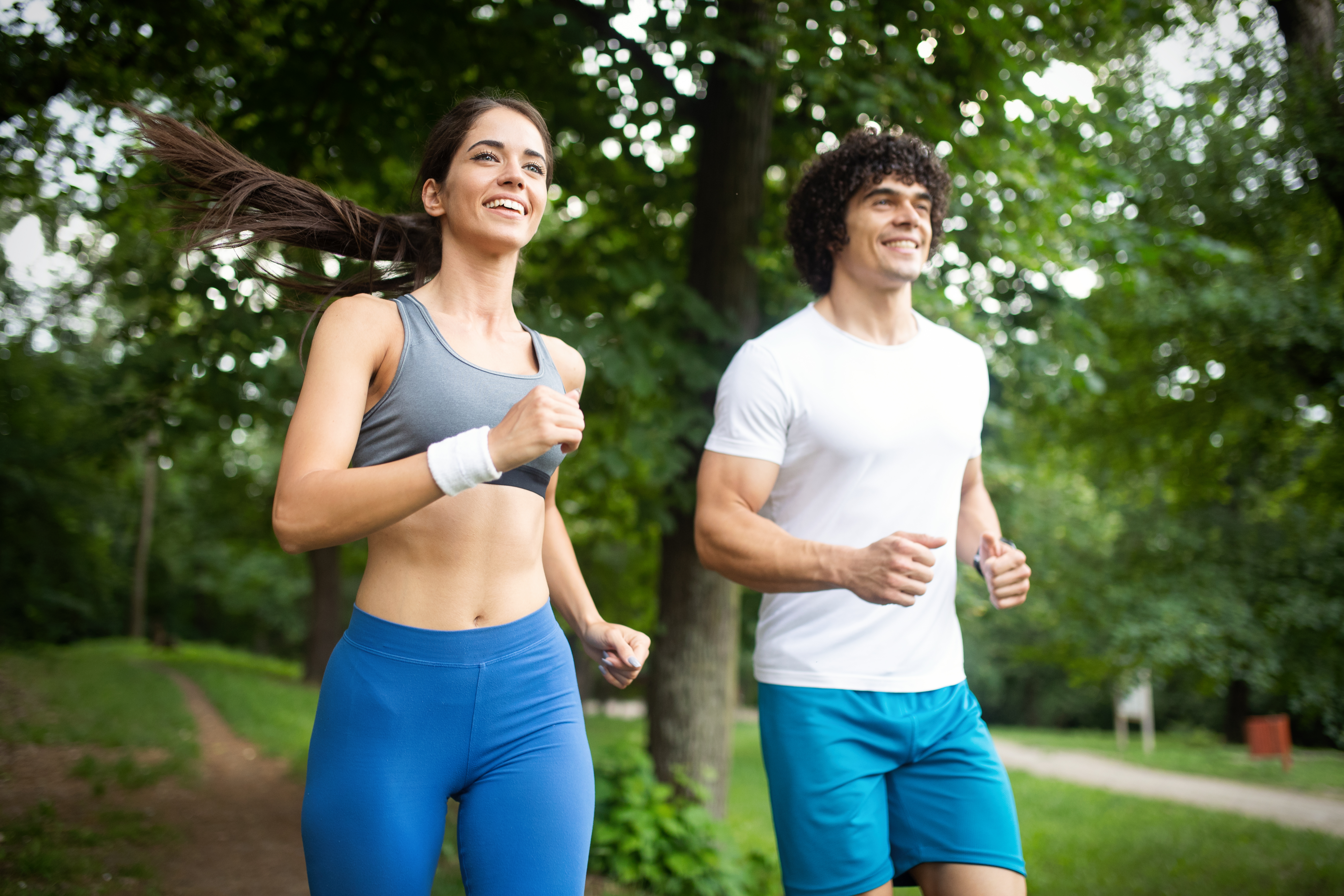 Canva - Happy young woman doing excercise outdoor in a park, jogging