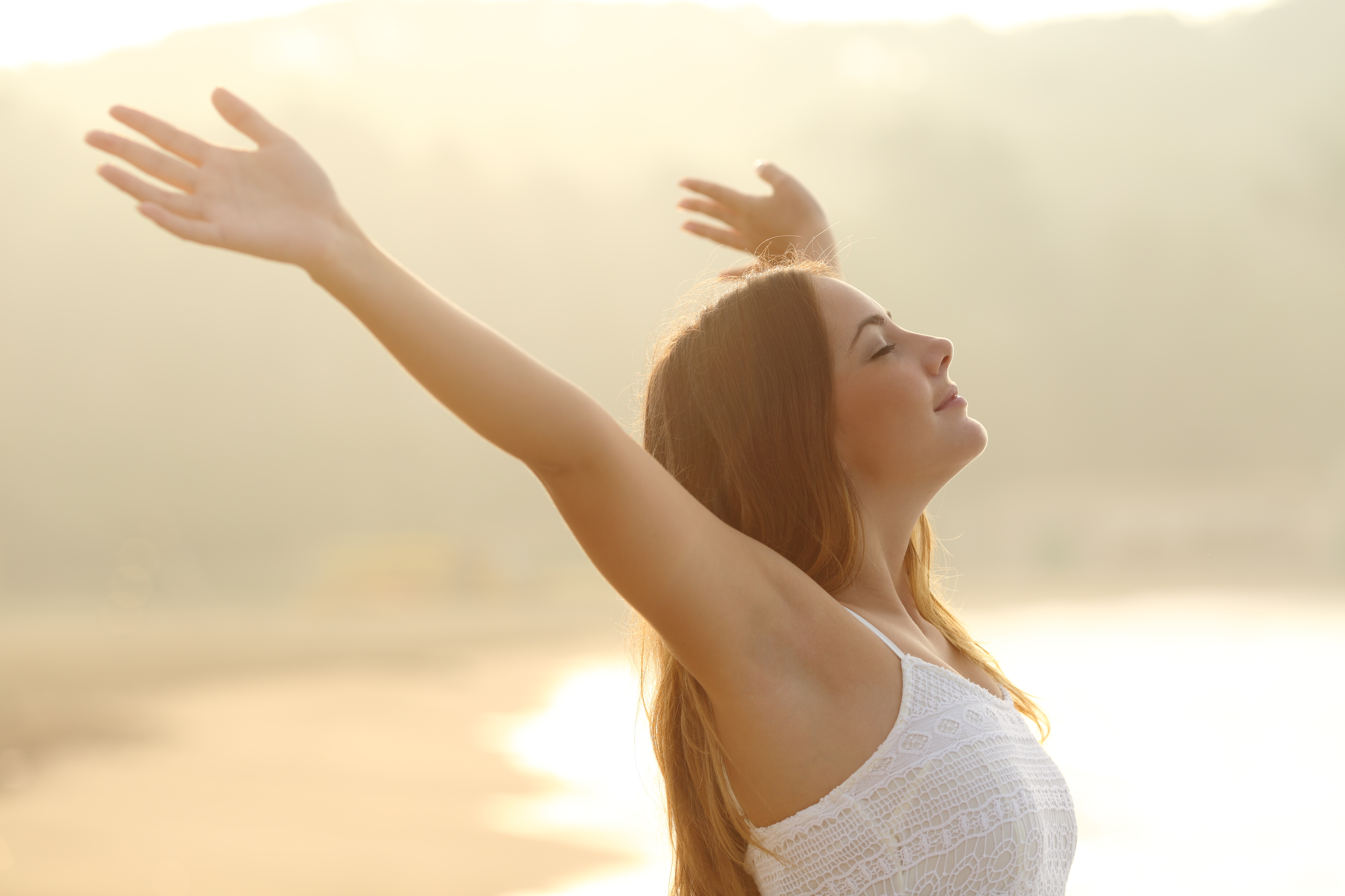 Canva - Relaxed woman breathing fresh air raising arms at sunrise