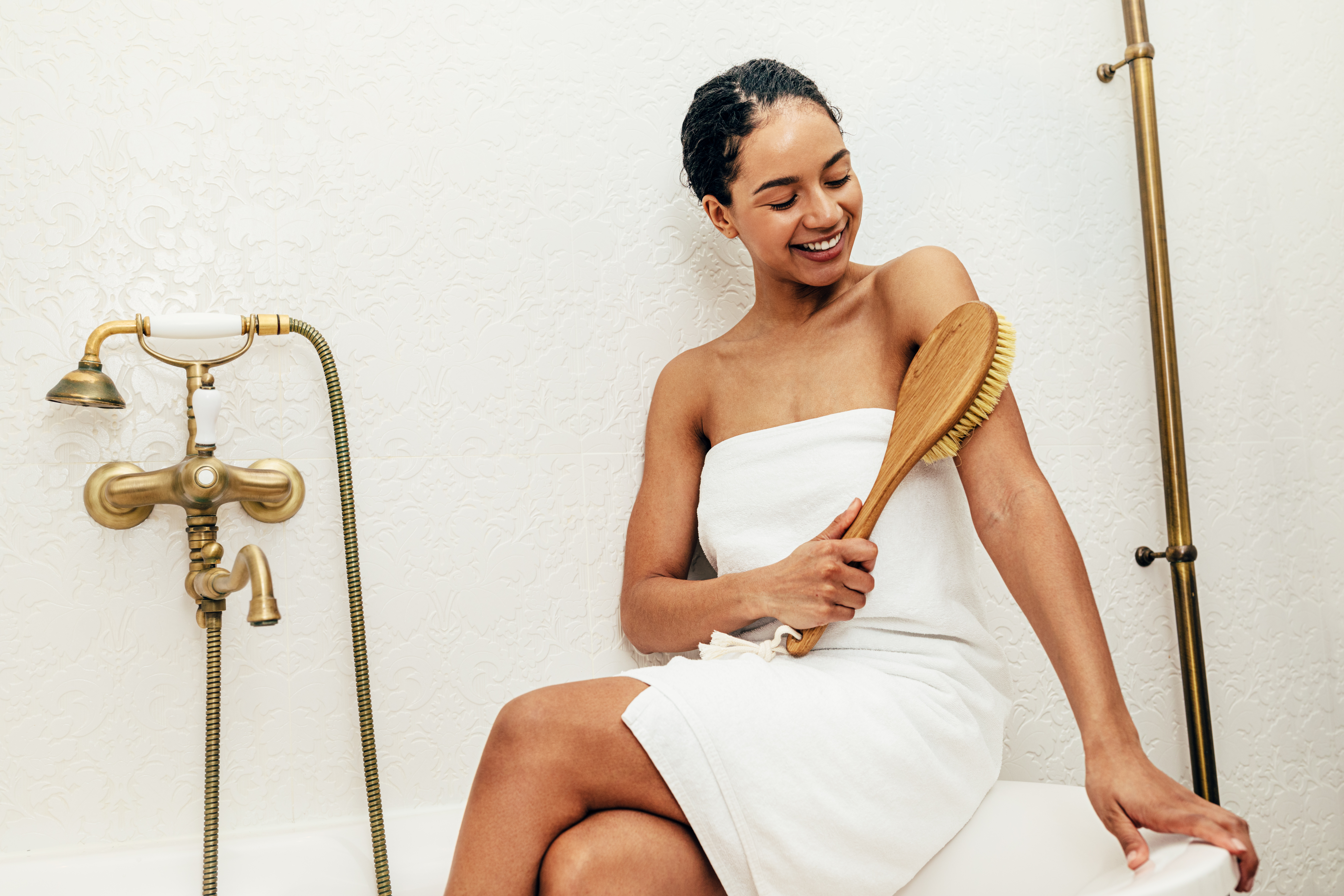 Canva - Smiling woman wrapped in white towel sitting on bath and dry brushing her arm