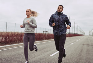 Canva---Diverse-Young-Couple-Running-along-a-Country-Road