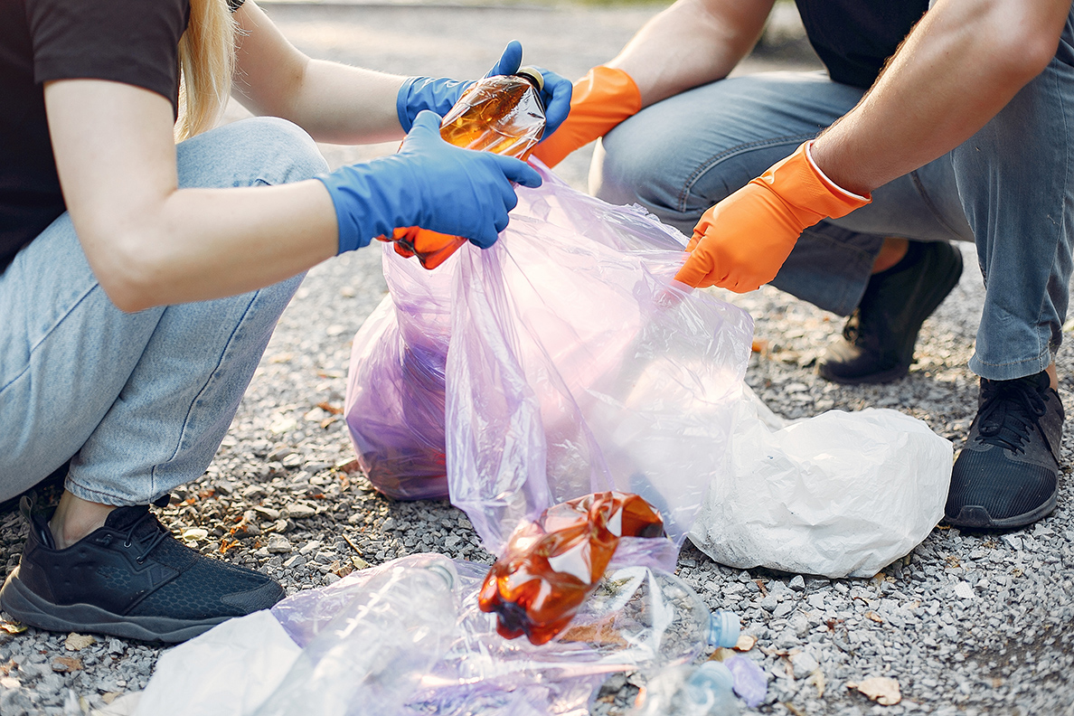couple-collects-garbage-in-garbage-bags-in-park-AECE6WN_envato