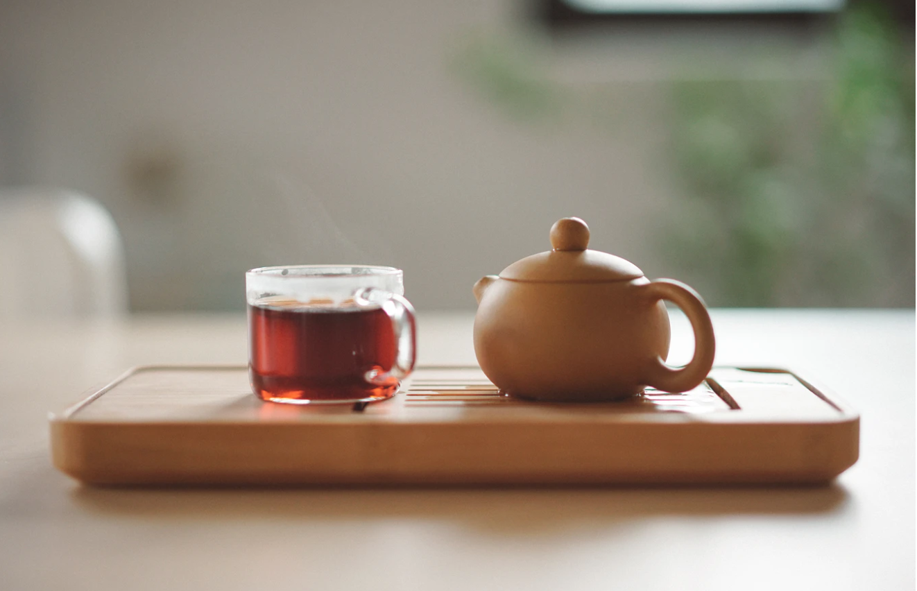 cup of tea and small teapot on wooden board