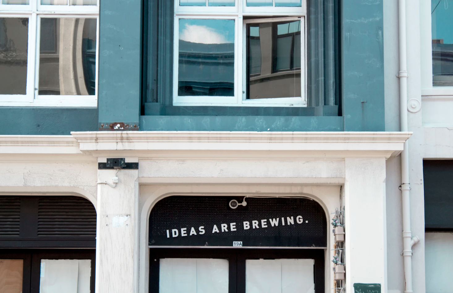 "front of a building with a sign on a door that reads ""ideas are brewing"""