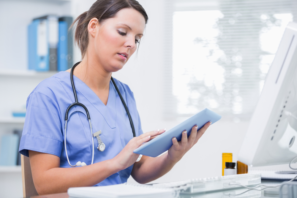 Side view of young female surgeon using digital tablet in front of computer at desk in clinic-1
