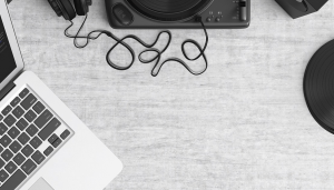 open laptop on gray table with headphones and turntable