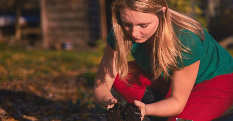 young woman examining soil